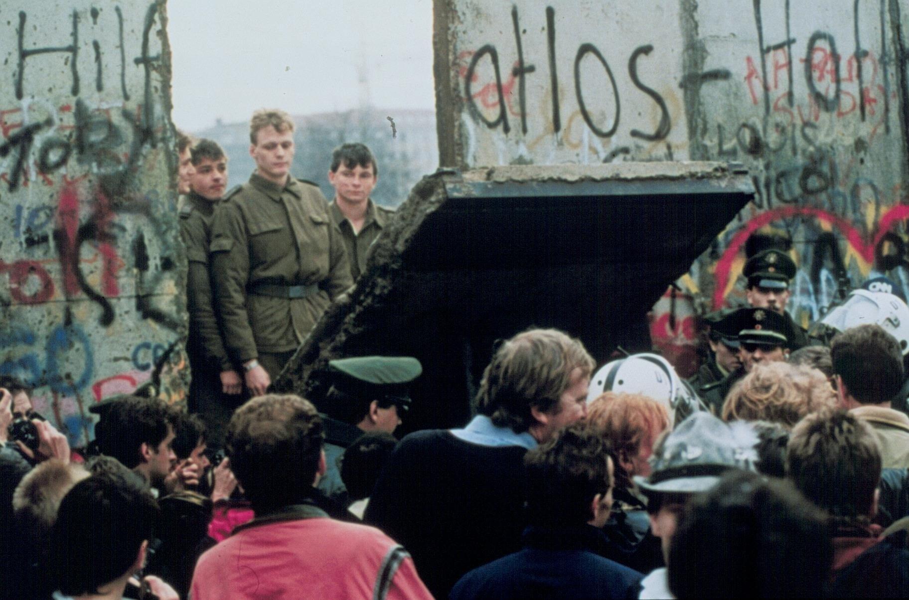 Foto di una porta murata del Muro di Berlino che viene abbattuta cadendo verso l'Ovest e rivelando il cordolo di soldati della parte Est.