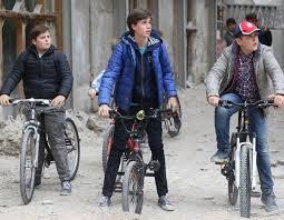 Tre ragazzi girano in bici tra le macerie de L'Aquila. Una scena tratta dalla serie 'L'Aquila, Grandi speranze'