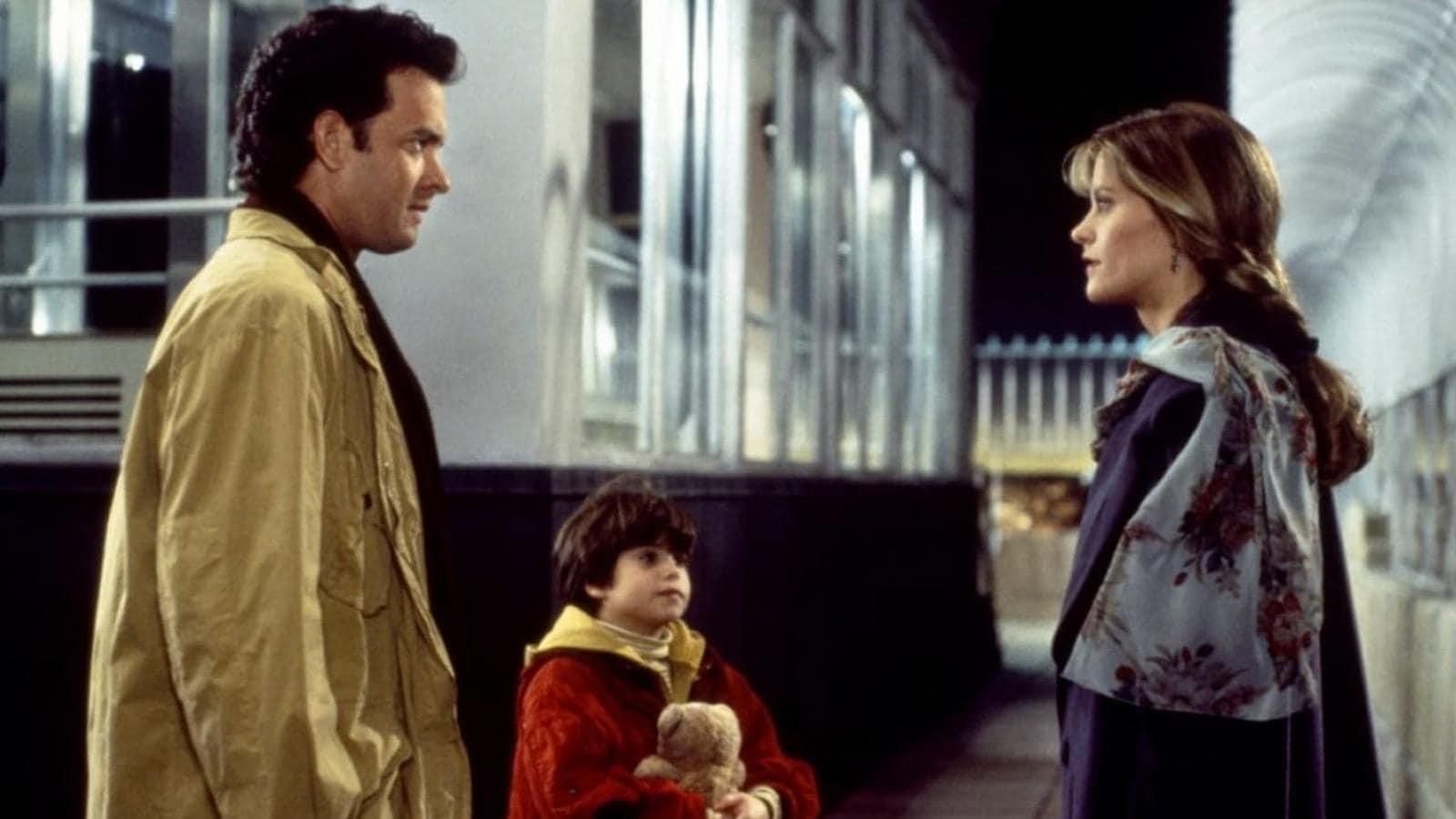 Sam Jonah ed Annie nella scena finale di Insonnia d'Amore. Jonah indossa stringe un peluche e guarda Annie. La donna e l'uomo si guardano negli occhi.